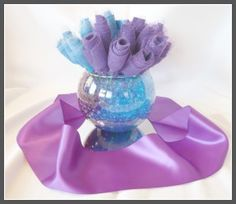 Want to incorporate your fundraising event color theme into a centerpiece design rich in color (and cheap in cost)? For this design, I used very inexpensive felt sheets along with a small amount of glittery accent tulle with floral picks for the flowers. Coordinating water pearls with a table mirror and accent ribbon tied the look together. All these materials can be purchased in bulk on Amazon.com. Ask your local florist if you can borrow the table mirrors for the night!