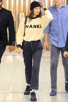 Bella Hadid rocks a Chanel sweatshirt and black striped pants as she arrives at the airport to catch a flight out of Milan, Italy Looks Street Style, Looks Style, My Style, Bella Hadid Outfits, Bella Hadid Style, Mode Outfits, Fashion Outfits, Womens Fashion, Fashion Clothes