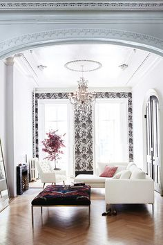 A hint of monochrome wallpaper and white walls. A white corner sofa and a few splashes of blush pink and burgundy.