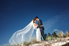 A beach wedding showing off the veil. Image by Dave (Danae Photography)