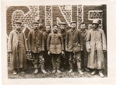 WW1: German POWs photographed by a news photographer. The lineup includes the very young, on the extreme left, the middle aged, in the middle, and the young.