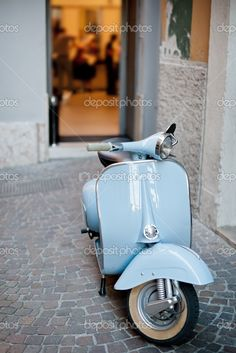 Lightblue Italian vintage Vespa scooter in a warm lighted evening scene at Rome, Italy