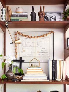 """""""Try hanging artwork between shelving to add dimension and break up the monotony of stacks of books. Be sure to call the artwork out; a wooden chain draped over the frame and a clip lamp both work hard to highlight the piece.""""Styling: Sally Breer"""