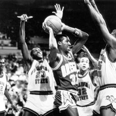 Black and white photo of University of Oregon basketball player Richard Lucas with the ball, trapped by a trio of Oklahoma State defenders during a game played at Memorial Coliseum in Portland on December 27, 1987 and won by the Ducks 68-55. ©University of Oregon Libraries - Special Collections and University Archives