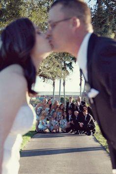 Fun group wedding photo with a bride and groom kiss. Amber Malia Photography