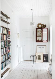 All-white entryway with floor-to-ceiling bookshelves and painted white plank floor.