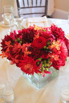 Wedding Centerpiece:  Red Dahlias, Burgundy Dahlias, Black Baccara Roses, Green Berzillia Berries, Red Mokara Orchids and Hot Pink Gloriosa Lilies    Ruby Reds Floral & Garden