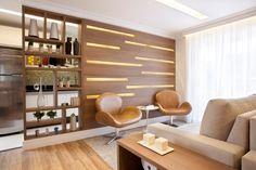 este projeto da arquiteta Adriana Fontana, a aliada para dividir o estar da cozinha, de forma a manter a conexão entre os dois ambientes, foi a marcenaria. Veja que os nichos no painel de madeira promovem a transparência mas preservam a privacidade de quem está na sala