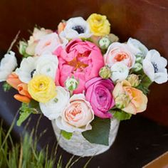 Rustic arrangement with coral peonies, assorted ranunculus, peach garden roses and white anemones