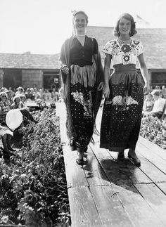 American socialite Elizabeth Fly (later Rohatyn) (left) and future First Lady Jacqueline Bouvier (later Kennedy, then Onassis) (1929 - 1994) walk on a makeshift catwalk and model beaded skirts at a fashion show, East Hampton, New York, July 1949.
