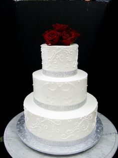 Batman Wedding Cake. white with silver piping and batman symbol. The roses on top would be perfect because we are doing red roses in centerpieces