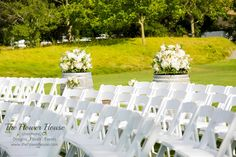 Winery wedding ceremony with barrels and large lush floral arrangements