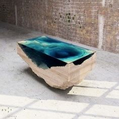 UK furniture designer, Christopher Duffy has layered glass and wood to form a dramatic table that replicates a geological cross-section of the sea.
