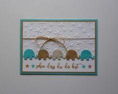 """Liebevoll gestaltete Karte zur Geburt """"Schön, dass du da bist"""". Grundfarbe der Karte ist türkis, abgesetzt in hellbraun und weiß. Die """"Elefanten-Reihe"""" greift diese Farben erneut auf, der weiße..."""