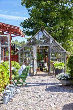Växthus med öppen dörr. Grusgång, krukor med blommor, gröna trämöbler och vattenkannor i zink på rad.