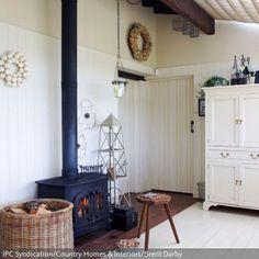 Der kleine Kaminofen steht feuerfest auf Terracotta-Fliesen und das Feuerholz wird in dem praktikablen Weidenkorb aufbewahrt. Ein Holzhocker steht als Sitzgelegenheit…