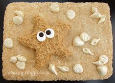 """Peanut Butter Fudge Starfish on a """"sandy"""" bed of rice krispies treats dotted with shells.  I am in LOVE with all of the great things over at Hungry Happenings!"""