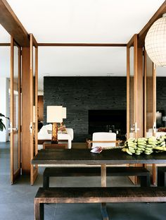 dark stacked stone fireplace + wood double doors + outdoor wood dining space + globe pendant via prue ruscoe