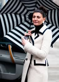 Giovanna Battaglia  - ivory coat trimmed with black,  black button detail, coordinating black striped umbrella. We love...