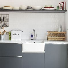 Understated kitchen cabinets, matched with a classic white butler sink, create a clean and modern look. Functionality is key here, the clue is in the stainless steel accents and easy-access open shelving. Minimal, industrial, utilitarian.