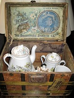 Lithographed small wooden doll trunk, apparently  advertising premium from the Brantford Starch Company of Brantford, Ontario, Canada, with an antique children's tea set and a tiny china doll. From Tracy's Toys (and Some Other Stuff).