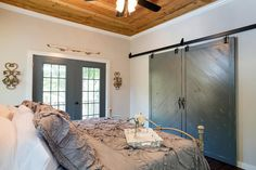 The master bedroom features natural wood-plank ceiling, architectural accents and closets concealed behind rustic barn doors.