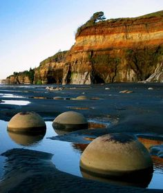 The mysterious sphere boulders on the blacksand low-tide-only beach north of the Tongaporutu River mouth, northern Taranaki Coast, The North Island, New Zealand New Zealand Beach, New Zealand Travel, Black Sand Beach Hawaii, River Mouth, Beach Wallpaper, Mysterious Places, Big Waves, South Island, Places Around The World