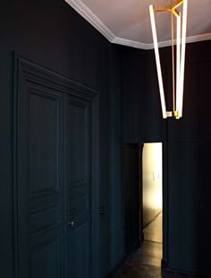 Little Parisian entryway adds drama and unifies a small space by painting walls, doors and trim in one uniform shade of navy. Designed by Karl Fournier and Olivier Marty of the Paris and Marrakesh based firm Studio Ko.
