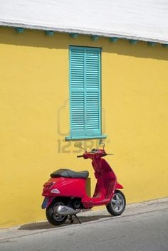 A brilliant red motorscooter parked next to a bright yellow stucco wall with teal green shutters of a Bermuda home.