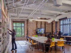 """LOVE the culture wall and the work table in the center with workstations outside.  SWA Group offices in San Francisco greets visitors with a """"Culture Wall,"""" which includes photos of people, inspiration, and work examples."""