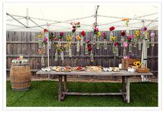 so cute!  hanging flower bottles over dessert table.