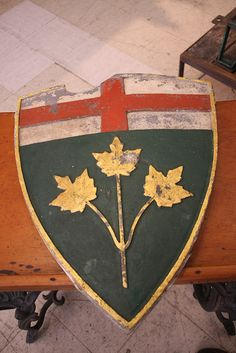 Coat of arms for the province of Ontario, Canada. The 3 golden maple leaves represent Canada, on a green background. On a chief is the Cross of St. George.