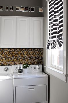 I like the idea of a fabric panel behind the washer and dryer to hide the hookups. Clever. And the hanging polaroids are cute, too.