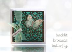 "(Supplies: Butterfly and brocade stamps, and pearls by Hero Arts.  Aqua Zing! embossing powder by American Crafts.  ""a little note"" by A Muse.  Ribbon by Martha Stewart.  Stick pins and neato safety pin by Making Memories.  Perfect Pearls, Tea Dy and Vintage Photo Distress inks by Ranger.  Copic Markers to color the butterfly.  A super quick how-to: I embossed the brocade on white cardstock, then rubbed the distress inks all over it using a sponge and wiped off the embossed parts with a baby…"