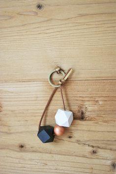 """Schlüsselanhänger mit Holzperlen in schwarz, kupfer und weiß. Von mir handbemalt und matt lackiert. Aufgefädelt auf ein goldfarben-braunes Wildlederband. Schlüsselring in bronzefarben. Erhätlich in meinem Shop """"Maclino"""" bei Dawanda für 8,90 €."""