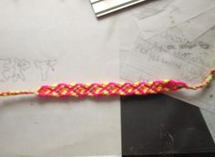 Friendship bracelet The colours of it are pink, yellow, green and orange