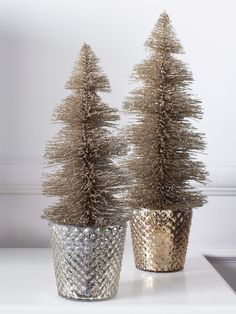 Silvery votives do double duty as pots for glittery little trees.