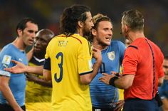 Diego Forlan of Uruguay and Mario Yepes of Colombia protest to...