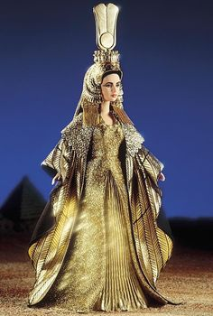 """suffragettebarbie: """" Elizabeth Taylor in Cleopatra™ Elizabeth Taylor as Cleopatra — her magnificent golden costume is re-created here in splendid detail. Cleopatra's luxurious gown has a dramatic """"feather"""" cloak that surrounds her like the wings of a. Elizabeth Taylor Cleopatra, Barbie I, Barbie World, Barbie Clothes, Barbie Blog, Vintage Barbie, Barbie Celebrity, Costume Carnaval, American Girl"""