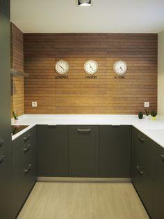 Cocina actual con revestimiento porcelánico imitación madera. Encimera en Krion. Proyecto de AZ Diseño.