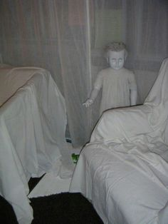 Creepy and inexpensive Halloween DIY decor. Get old dolls from the thrift store and spray paint them white - surround with cheese cloth shrouds.