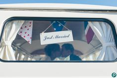 The bride and groom kiss in the back of the vintage VW camper van at Bournemouth beach, in Dorset.    Wedding photojournalism by Dorset based wedding photographer Paul Underhill.