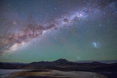 En esta postal de la Tierra, el núcleo central de la Vía Láctea se eleva sobre la meseta de Atacama, en el norte de Chile. A una altitud de 4.500 metros, la extraña belleza del desolado paisaje podría pertenecer a un otro mundo. Sobre las playas planas de sal blanquecina de la región del Salar de Aguas Calientes hay parches sulfúricos amarillos y rojizos. Extendiendo la vista por el espacio extragaláctico, la Gran y la Pequeña Nube de Magallanes, que son galaxias satélite de la Vía Láctea,