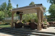 Free-standing solid roof patio cover with drapes