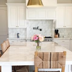 Love all of the bright white in this kitchen. The gold light fixture and wooden chairs really pop.