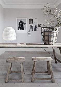 Stoere houten eettafel met bijpassende krukjes. Mooie lichtgrijze muur met zwart/wit foto's op achtergrond.