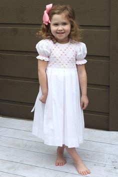Great princess dress by Strasburg Children. This heirloom dress with box pleats includes smocking and adorable pink accents. Sure to bring a smile to any girls face on Christmas morning.