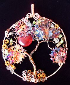 "Check out the colors. <3     Wire wrapped copper Tree of Life Suncatcher. There are five different tones of non-tarnish copper wire. The leaves constructed withcolorful copper splashes. It has a Carnelian moon and further embellished with accents of Citrine and Peridot chip beads. Measures 3 - 1/2""."