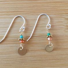 A 14K gold filled disk shines beneath a stack of sunstone and turquoise beads. These beads are wire-wrapped by hand with Sterling silver wire and hang from Sterling silver earwires. These are delicate but luminous earrings. Check out more WildGingerJewelry: https://www.etsy.com/shop/WildGingerJewelry?ref=hdr_shop_menu
