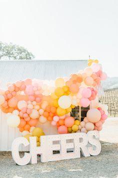 A colorful marquee and balloon backdrop. Photo: @jessicasofranko Balloon Installation, Balloon Backdrop, Ceremony Backdrop, Summer Wedding Colors, Floral Event Design, Wedding Balloons, Whimsical Wedding, Vineyard Wedding, Wedding Shoot